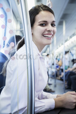 Interior : Portrait of young businesswoman sitting on the subway and looking at the camera