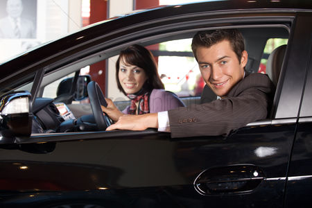 Transportation : Portrait of young couple sitting in a new car at showroom