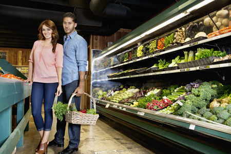 Supermarket : Portrait of young couple standing with vegetable basket in supermarket