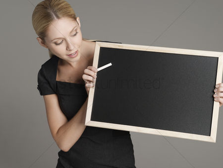 Black background : Portrait of young female teacher holding blackboard