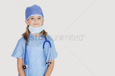 Camera : Portrait of young girl in surgeon s costume against gray background