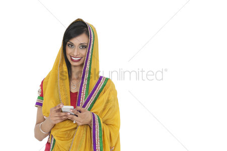 Traditional clothing : Portrait of young indian woman in traditional wear holding cell phone against white background