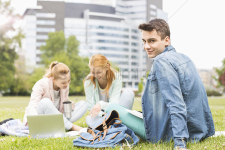 University : Portrait of young man with female friends studying on university campus