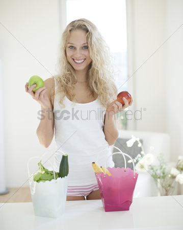 Czech republic : Portrait of young woman holding apples at kitchen counter