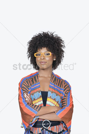 Traditional clothing : Portrait of young woman in african print attire standing hands folded over gray background