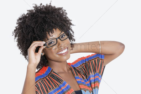 Traditional clothing : Portrait of young woman in african print attire wearing glasses over gray background