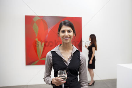 Interior background : Portrait of young woman in front of painting in art gallery