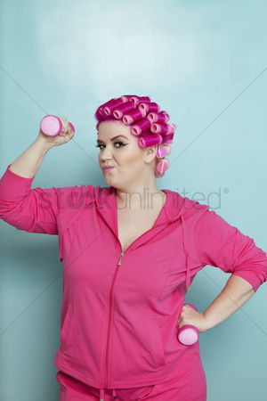 Dumbbell : Portrait of young woman lifting weights over colored background