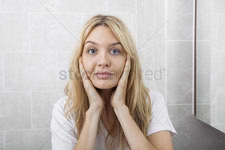 Examination : Portrait of young woman touching cheeks in bathroom