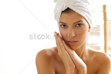 Spa : Portrait of young woman wrapped in towel with hands clasped