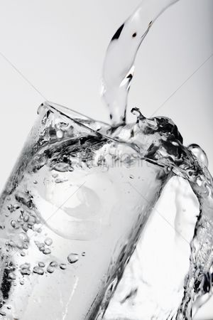 Refreshment : Pouring water into drinking glass with ice