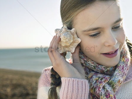 Pre teen : Pre teen girl listening to seashell standing on beach close up