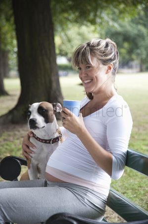 Hot dog : Pregnant woman on park bench with dog