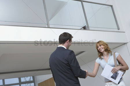 Satisfaction : Real estate agent shaking woman s hand in new home
