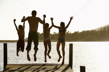 Summer : Rear view of father and children jumping off a pier holding hands