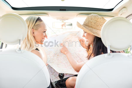 Transportation : Rear view of happy female friends reading map in car