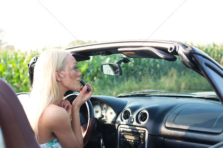 On the road : Rear view of woman applying lipstick in convertible