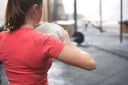 Fitness : Rear view of woman holding medicine ball in crossfit gym