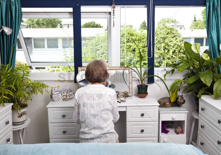 Houseplant : Rear view of woman sitting at dresser in bedroom