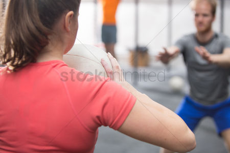 Fitness : Rear view of woman throwing medicine ball towards man in crossfit gym