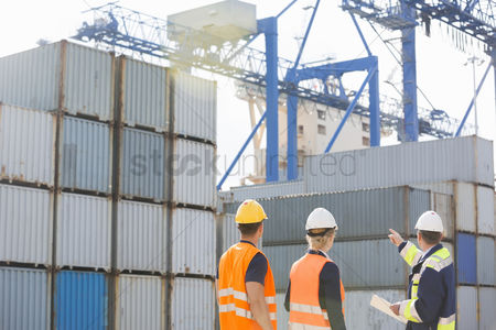 Supervisor : Rear view of workers inspecting cargo containers in shipping yard