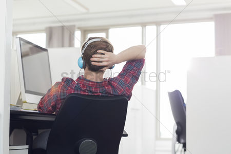Creativity : Rear view of young businessman wearing headphones at computer desk in office