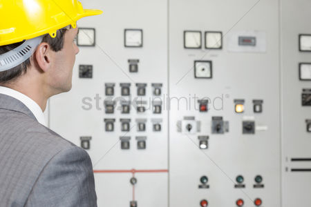 Supervisor : Rear view of young male supervisor examining control room in industry