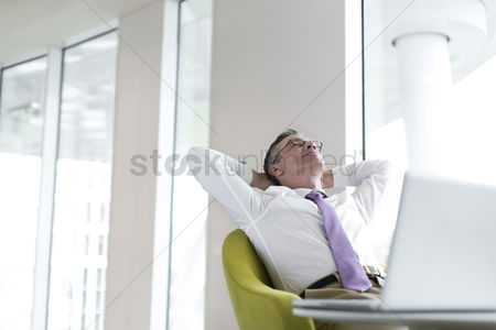 40 44 years : Relaxed mature businessman reclining at lobby