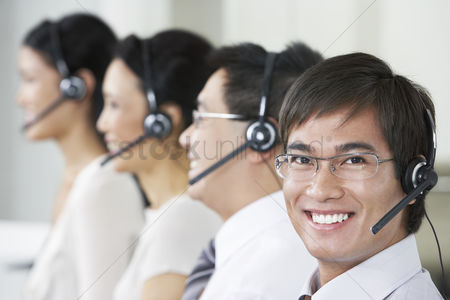 Assistance : Row of customer service representatives wearing telephone headsets in office head and shoulders