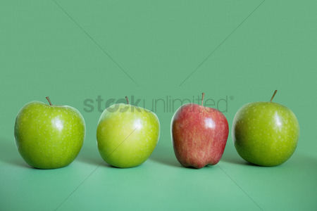 Food : Row of red and green apples over colored background