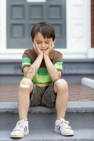 Steps : Sad little boy sitting on front steps of house