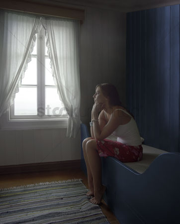 Loss : Sad woman sitting alone in room daydreaming side view