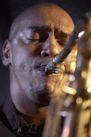Blowing : Saxophone player on stage portrait close-up