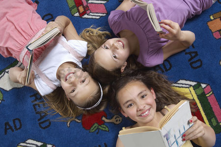 Pre teen : School girls reading books on floor in library
