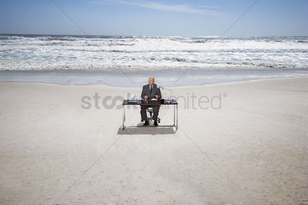 Bald : Senior business man sitting at office desk on beach elevated view