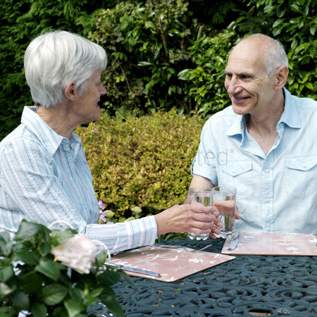 Outdoor : Senior couple holding glasses of water