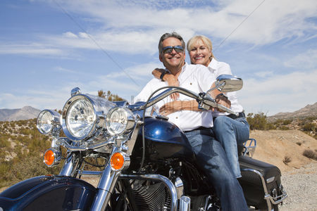 Trees : Senior couple on desert road sitting on motorcycle looking at camera