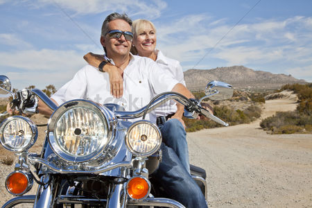Smiling : Senior couple on desert road sitting on motorcycle