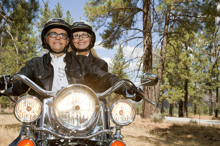 Jacket : Senior couple riding motorcycle through a forest