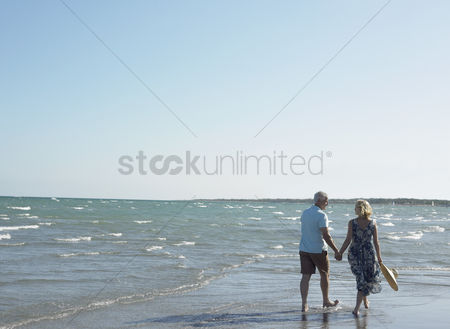 Two people : Senior couple walking on beach back view