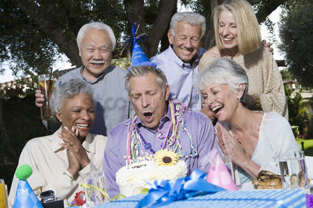 Blowing : Senior couples celebrating birthday party in garden