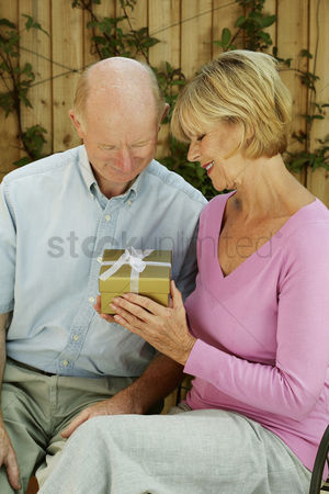 Birthday present : Senior lady holding a gift sitting beside her husband