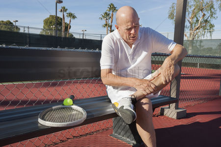 Bald : Senior male tennis player with leg pain sitting on bench at court