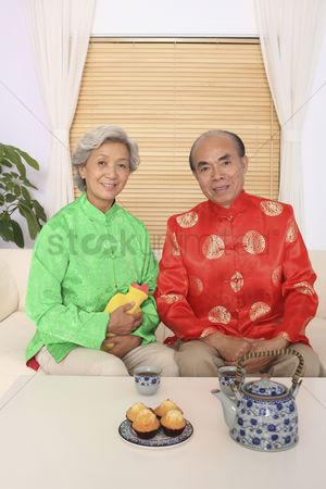 Tea pot : Senior man and senior woman in traditional clothing posing for the camera