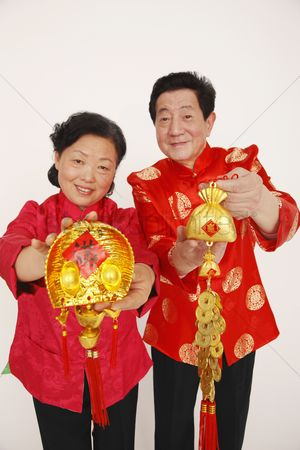 Traditional clothing : Senior man and woman holding chinese decorations