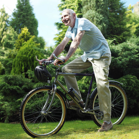 Aging process : Senior man cycling in the park
