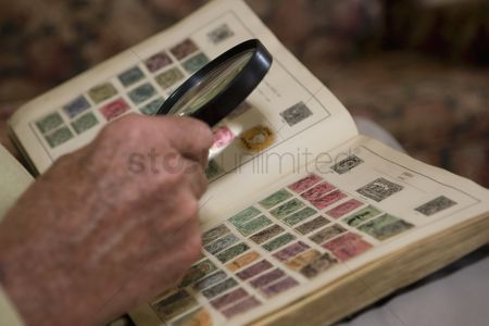 Collection : Senior man looks at stamp collection with magnifying glass