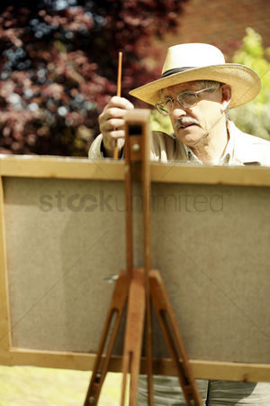 Bespectacled : Senior man measuring with a paintbrush while drawing