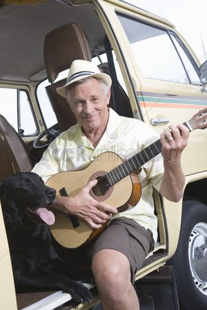 On the road : Senior man sits in his campervan with a guitar and his pet dog