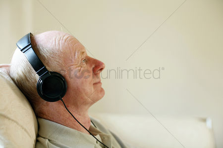 Retirement : Senior man sitting on the couch listening to music on the headphones